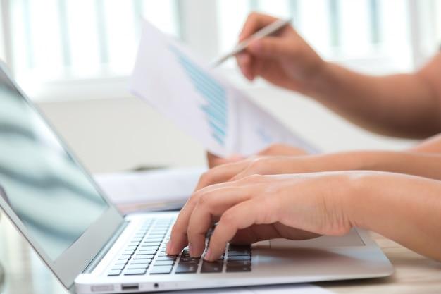 Close-up de l'employé travaillant avec un ordinateur portable dans le bureau