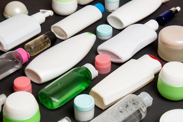 Close-up ensemble de bouteilles et bocaux de tailles différentes pour les produits cosmétiques sur fond coloré