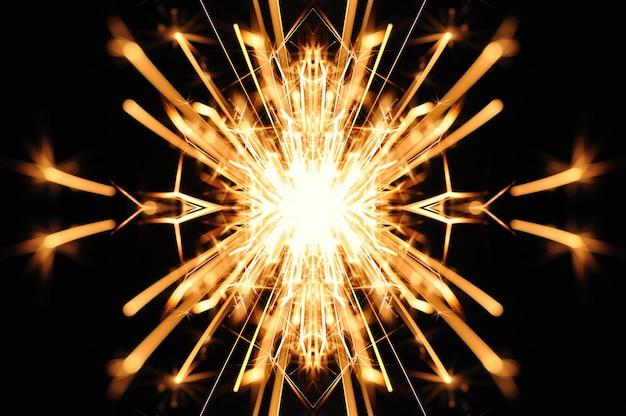 Close-up des étincelles dorées volent d'une bougie allumée sur un fond noir
