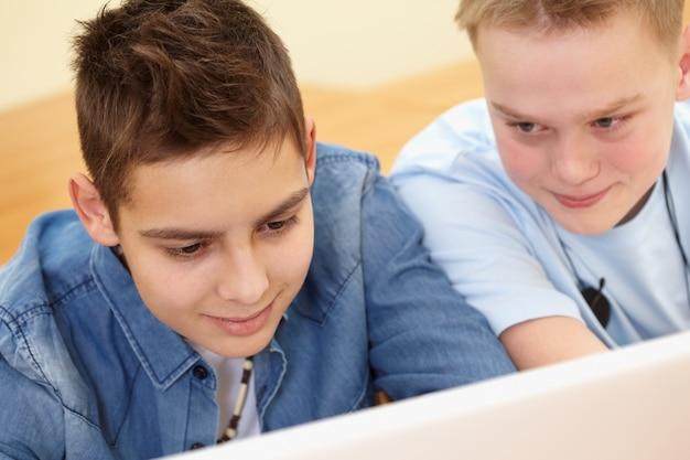 Close-up d'étudiants avec l'ordinateur à l'école