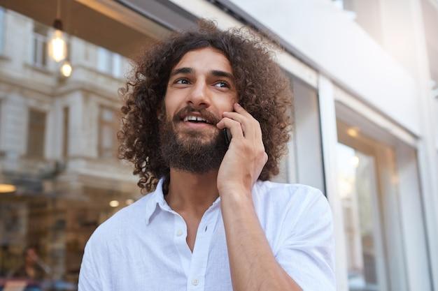 Close-up extérieur de charmant jeune homme barbu aux cheveux bruns bouclés, parler au téléphone avec un large sourire et à l'écart