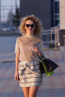 Close up fashion lifestyle portrait jeune fille hipster, avec des sacs à provisions sortant de la boutique.