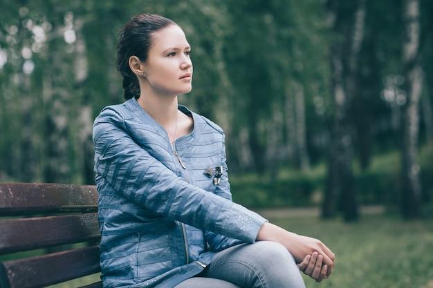 Close up.fashionable belle femme assise sur un banc de parc