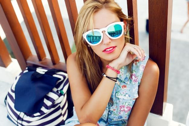 Close-up d'une femme blonde avec des lunettes de soleil blanches