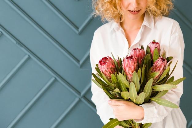 Close-up femme blonde tenant un beau bouquet