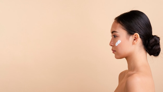 Close-up femme brune à la crème et copie-espace