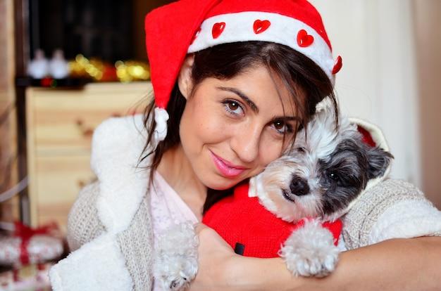 Close-up de la femme avec chapeau de père noël posant avec son chien