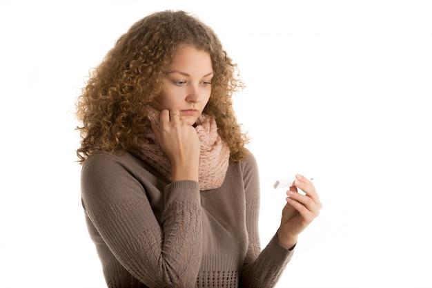 Close-up de la femme inquiète avec un thermomètre