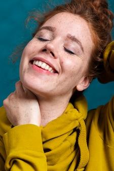 Close-up femme avec large sourire et taches de rousseur