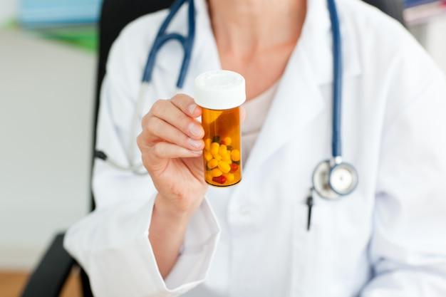 Close-up d'une femme médecin tenant des pilules dans l'appareil photo