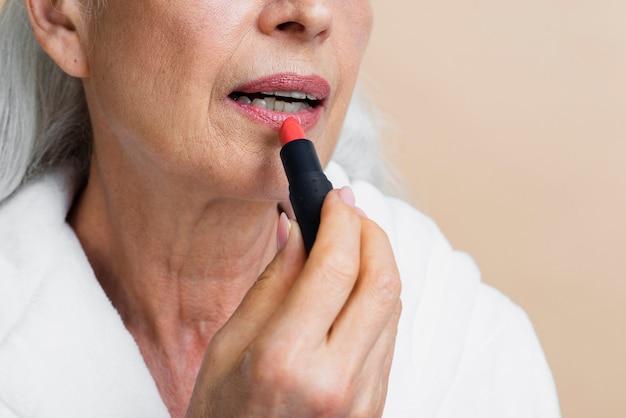 Close-up femme mûre appliquer du rouge à lèvres
