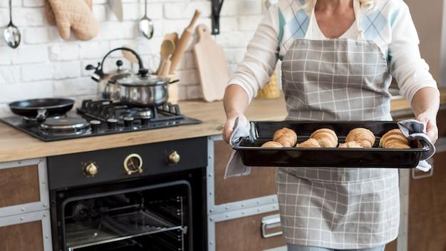Close-up femme portant un plateau avec des croissants