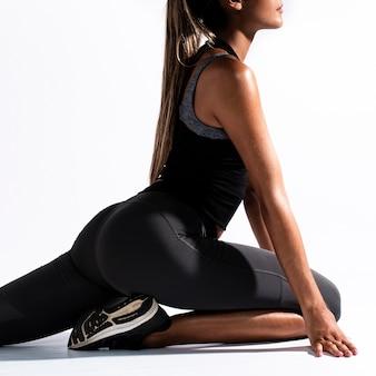 Close-up femme qui s'étend de jambes
