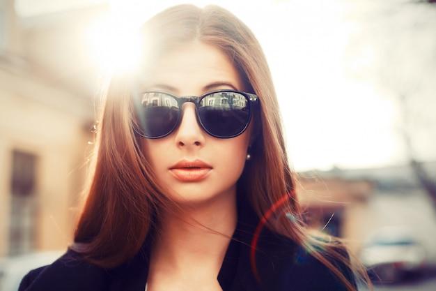 Close-up d'une femme sérieuse avec des lunettes de soleil au coucher du soleil
