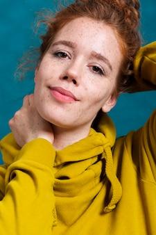Close-up femme avec des taches de rousseur et capuche jaune