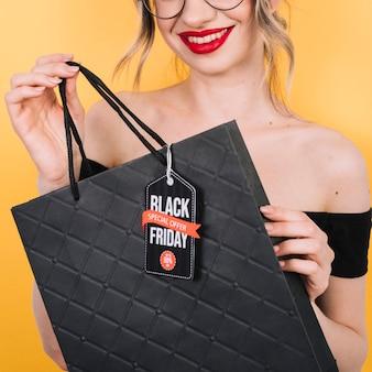 Close-up femme tenant un sac avec un design noir vendredi