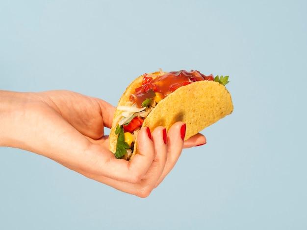 Close-up femme tenant un taco avec fond bleu