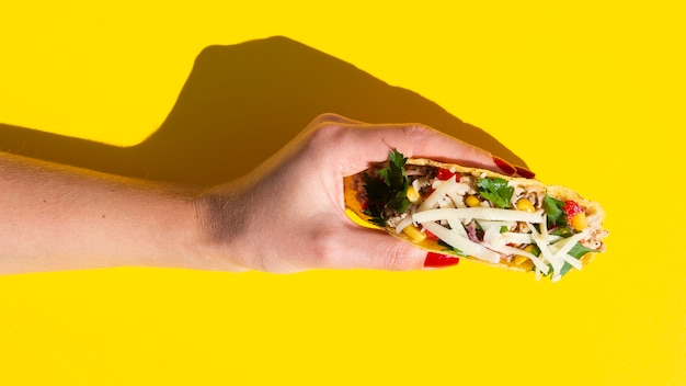 Close-up femme tenant un taco avec fond jaune