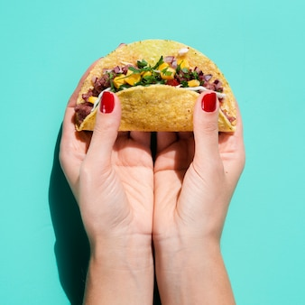 Close-up femme tenant taco avec fond vert