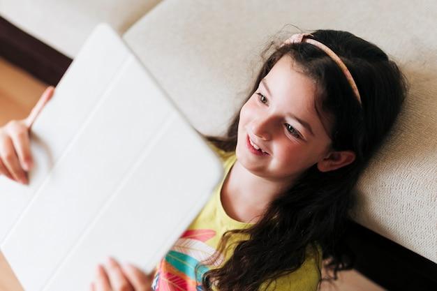 Close-up fille heureuse, brandissant sa tablette