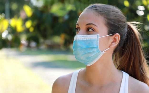 Close up fitness girl portant un masque chirurgical dans le parc à la recherche sur le côté.