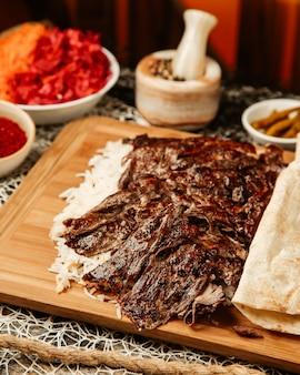 Close up fo lamb doner kebab place sur du riz servi avec du pain plat