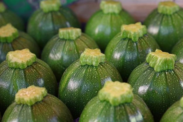 Close up frais nouveau bébé vert courgettes rondes d'affilée dans la case sur l'affichage de détail du marché de producteurs, high angle view