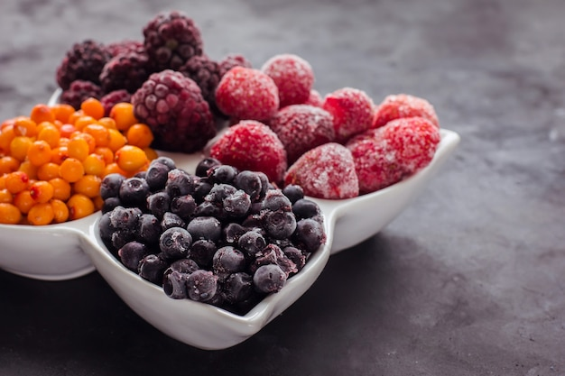 Close up de fruits et de baies surgelés sur un tableau noir des aliments sains vitamines snack dessert