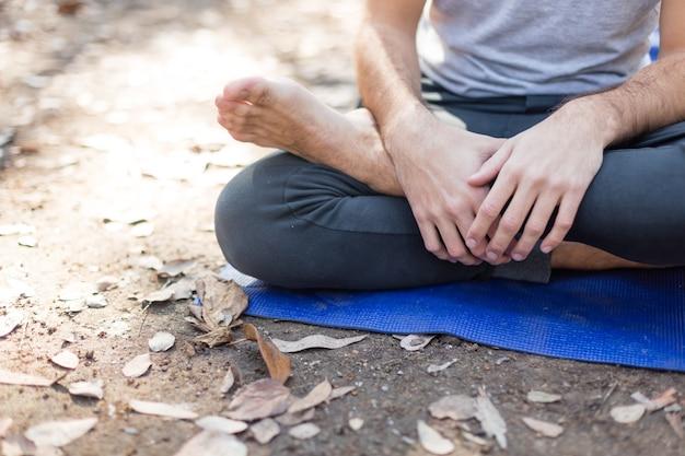 Close-up d'un garçon assis les jambes croisées