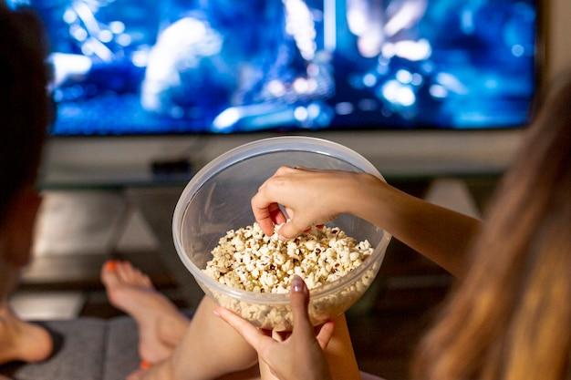 Close-up gens mangeant du pop-corn dans le salon