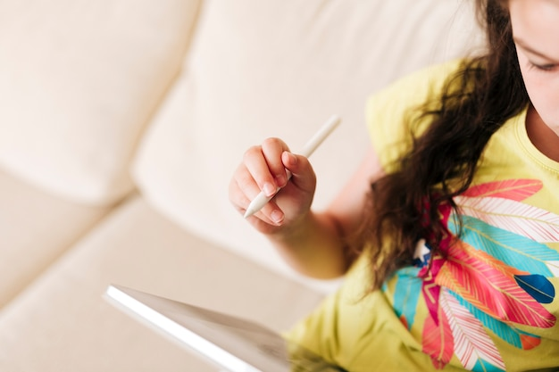 Close-up girl assise sur le canapé avec tablette et stylo