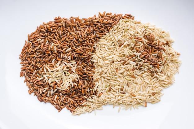 Close up de grains bruns et blancs mélangés dans une assiette blanche créant le ying et le yang