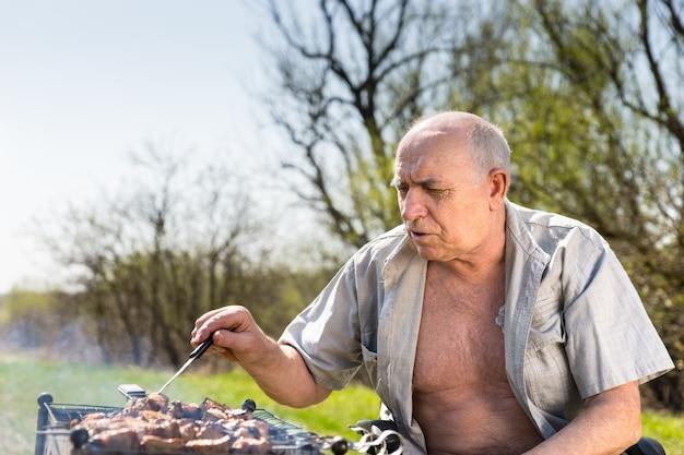 Close up grave vieil homme avec chemise ouverte griller dans la zone du camp tout en étant assis sur son fauteuil roulant sur un matin très ensoleillé.