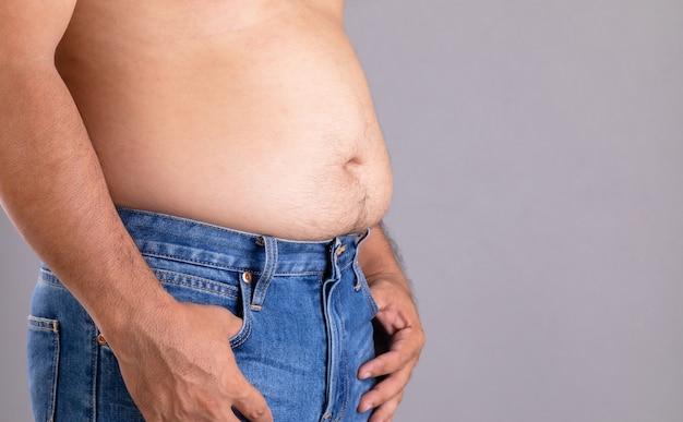 Close up gros homme debout et montrer son ventre avec. gens gras et concept sain