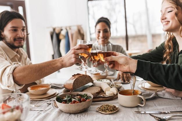 Close up groupe d'amis internationaux assis à la table pleine de nourriture tenant des verres de vin dans les mains
