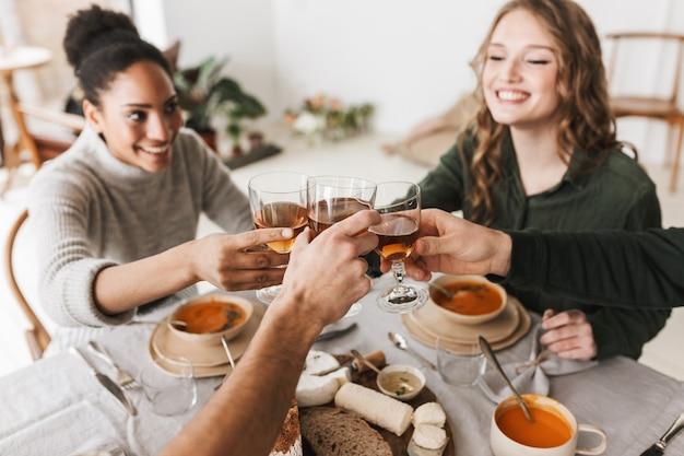 Close up groupe d'amis internationaux assis à la table avec des verres de vin dans les mains