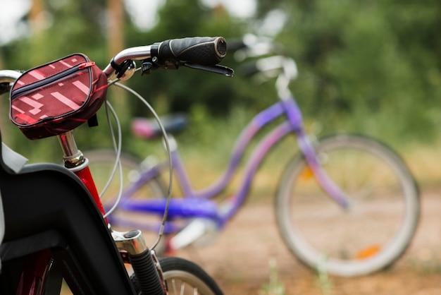 Close up guidon de vélo avec un vélo défocalisé