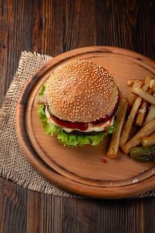Close-up de hamburger fait maison avec du bœuf, des tomates, de la laitue, du fromage et des frites sur une planche à découper