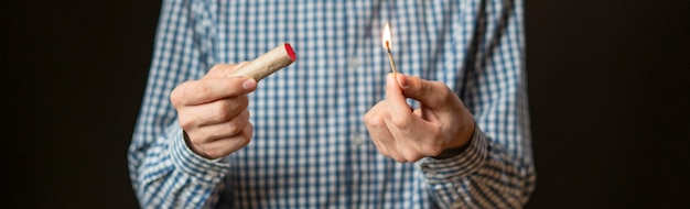 Close up hand hold cracker et le feu sur fond sombre isolé f