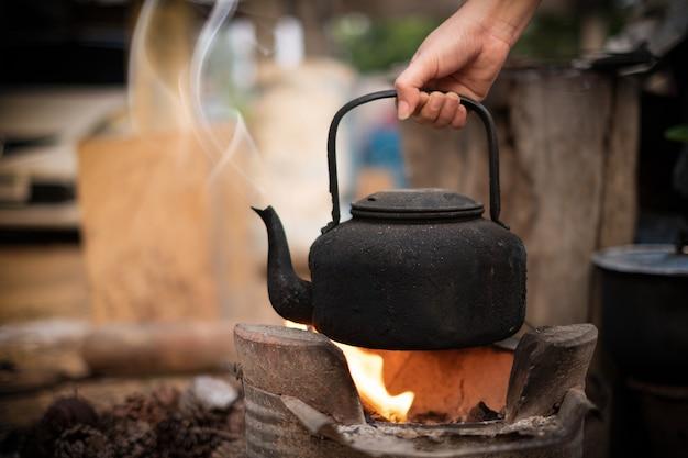 Close up hand holding faire bouillir de l'eau vieille bouilloire sur le feu avec un poêle à charbon à l'arrière-plan flou