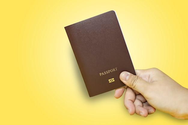 Close up hand holding passeport en marron avec fond jaune, passeport utilisé pour les voyages internationaux, isolé sur fond jaune. chemin de détourage de passeport.