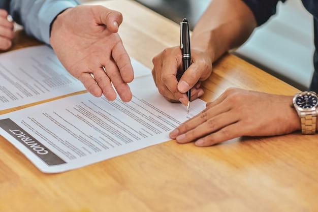 Close up hand holding pen signe un contrat sur le document