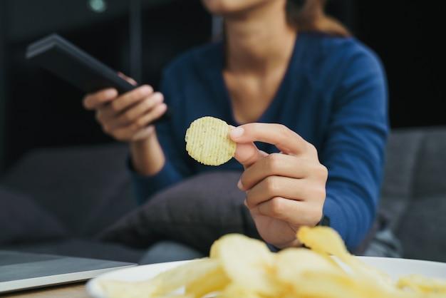 Close-up hand holding snack regarder la télévision dans le salon