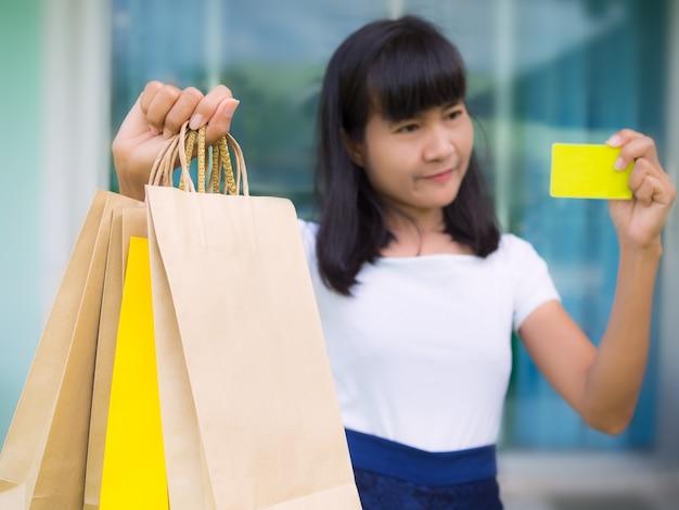 Close up hand of woman holding sac en papier et carte de crédit comme concept black friday