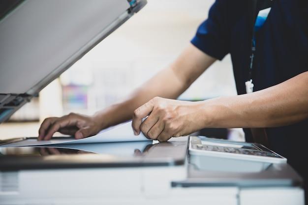 Close up hand office man numérisation des papiers sur le copieur.