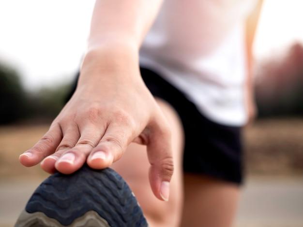 Close up hand stretching jambe et pieds avant une séance d'entraînement