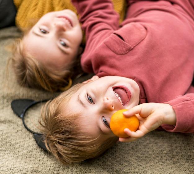 Close-up happy kids avec clémentine