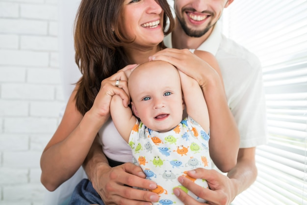 Close-up heureux jeune maman de famille et fils de six mois jouent et discutent le week-end.