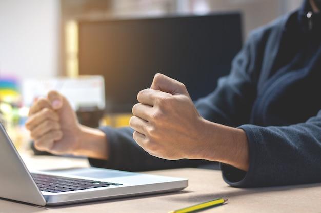 Close-up homme d'affaires avec les poings levés, assis à son bureau. célébrer le succès