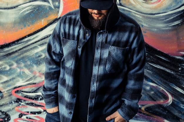 Close-up d'un homme devant le mur de graffitis